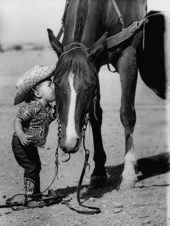 Little girl kissing horse.